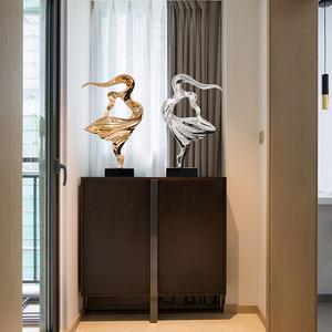 电视柜旁不锈钢雕塑摆件